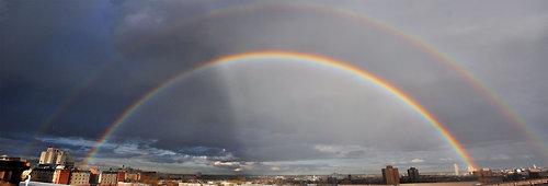 double rainbow over city